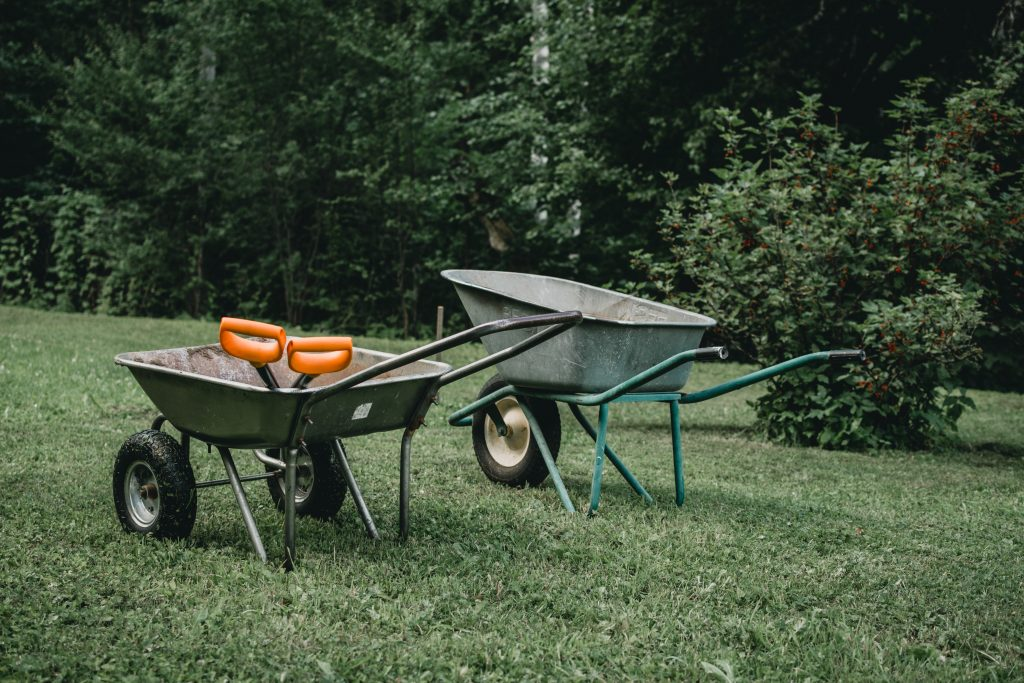 two wheelbarrows and garden tools