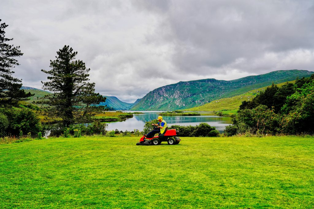 Man mowing lawn in front of lake